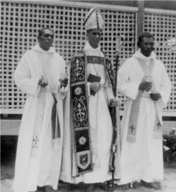 Two Ttorres Strait Islander graduating priests in white robes and bare feet with a bishop in full church regalia.