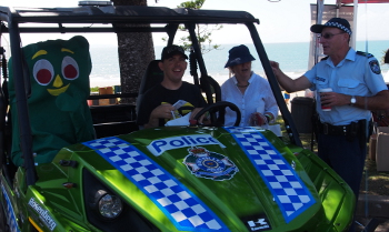Big Day Out attendee sitting in special green police vehicle with Gumby cartoon character.