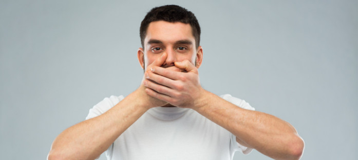 Man holding his hands over his mouth in the 'speak no evil' pose.