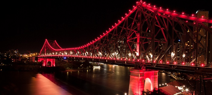 A large bridge crossing a river lit with maroon coloured lights