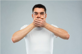Man with hands over his mouth in the 'speak no evil' pose