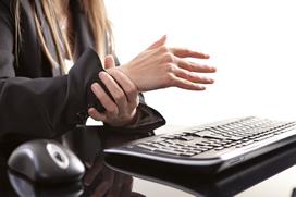 Woman at keyboard clutching a painful wrist