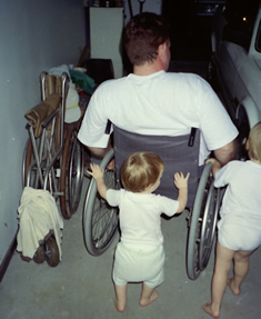 Two toddlers pushing a man in a wheelchair