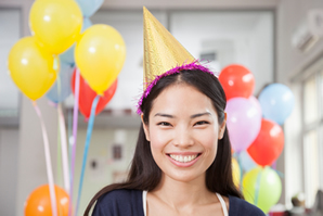 Young woman with balloons and party hat